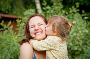 Happy young woman being kissed by a cute little girl; Shutterstock ID 108519002; PO: aol; Job: production; Client: drone